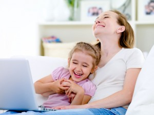 Mom & daughter with computer having fun